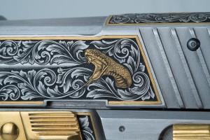 Close up of gold inlaid cobra on Sig Sauer slide